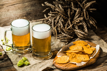 Two beer mugs with hops and chips and wheat on linen cloth