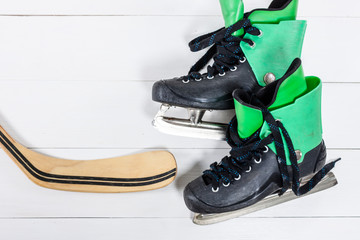 Overhead view of hockey stick and ice skates on white wooden tab