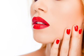 Close up of sexy woman lips with red lipstick and red manicure
