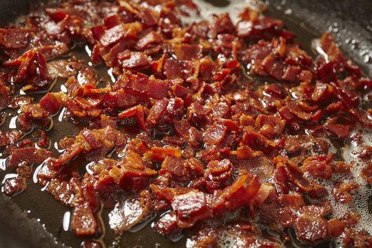 pieces of bacon frying in a skillet
