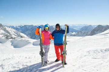 Couple skiing in the mountains on a sunny winter day