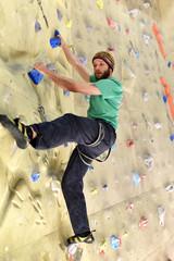 Bouldersport: Sportler klettert in einer Halle an einer künstlichen Kletterwand