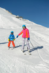 Smiling little boy with family learns skiing during winter vacations.