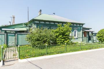 Дом с деревянными украшениями в зелени