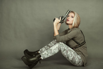 Indoor portrait of young adult girl dressed in military style clothes sitting and holding revolver close to shoulder and face