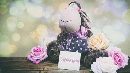 plush lamb and pink roses and a wooden background, a note on the