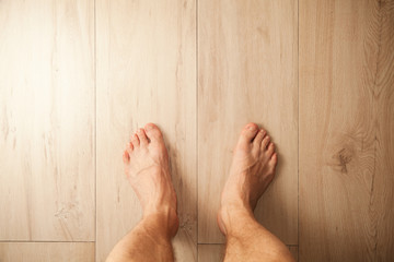 Male feet stand on wooden floor