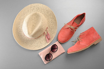 Red shoes, straw hat and sunglasses on grey background