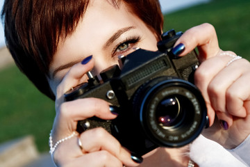 Red-haired girl with green eyes taking pictures camera in the city park.