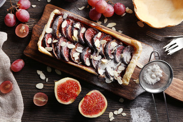 Delicious fig cake with almond flakes on wooden cutting board