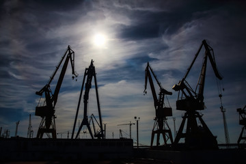 Beautiful landscape of  cranes in shipyard against a backlight in coast of Huelva, Andalusia, Spain.
