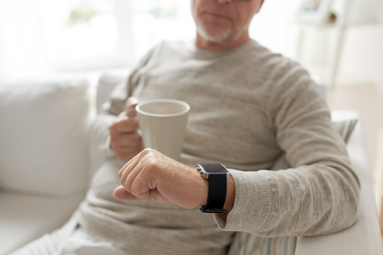 close up of old man with mug looking at wristwatch