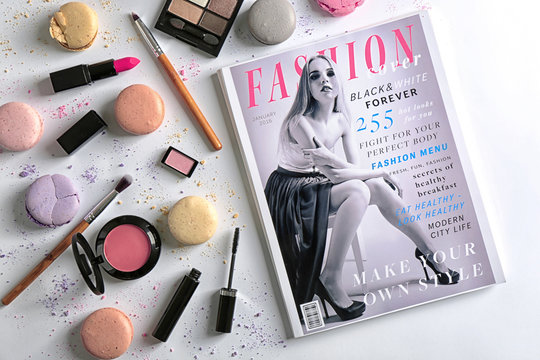Makeup products, magazine and macaroons on light background