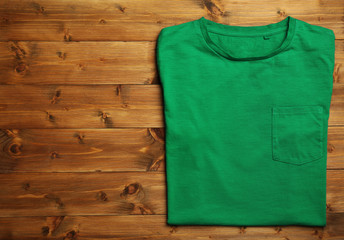 Blank green t-shirt on wooden background