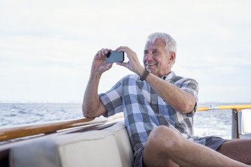 Senior man on a boat trip taking a picture