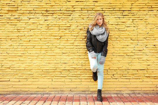 Young beautiful woman standing on yellow brick wall background