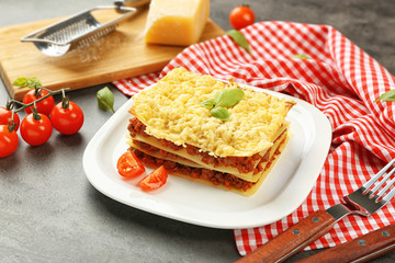 Plate with tasty lasagna on grey table