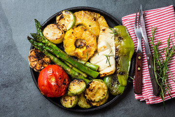Grilled vegetables, pineapple slices and fresh cheese on iron plate