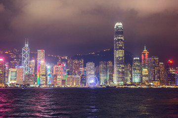 Skyline night view of tall buildings from across Victoria Harbor