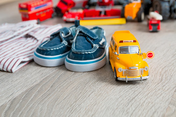 School bus toy near shirts and blue boat shoes on grey wooden background. Boy outfit. Close up.
