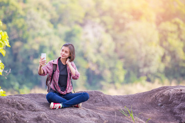 Happy young woman pictures of herself with smartphone in nature