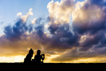 Silhouettes of young girls sitting during sunset and take a selfie with smartphone.