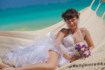 Bride lying in a hammock on the beach