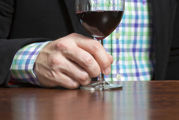 Business man is enjoying a glass of red wine.
