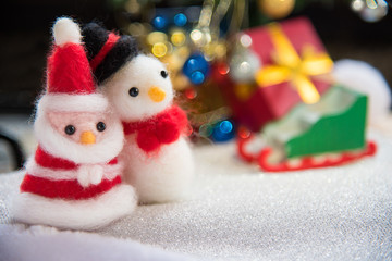 Santa claus and snowman wool doll on snow set up with xmas tree,