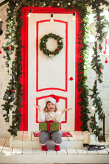 funny girl child gnome in santa hat with gift on  porch of house