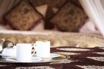 Two turkish coffee cups with oriental canopy bed at the backgrou