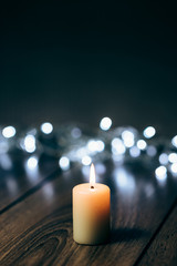 Burning candle on a table with Christmas decorations