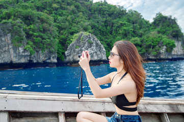 Young woman taking photo of beautiful sea on camera.
