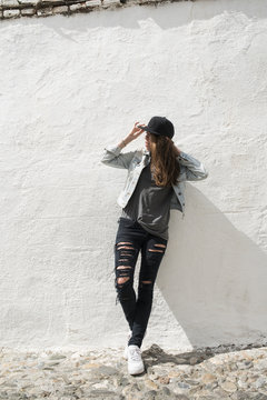 Young trendy woman against shabby wall