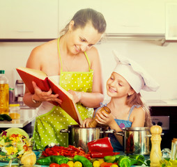 woman and daughter preparing food consulting the cookbook