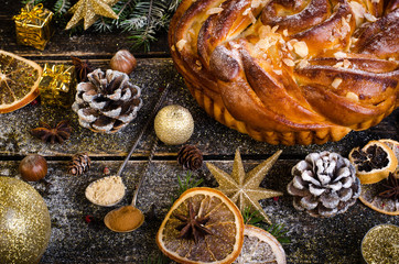 Christmas background - cake, stars, dry oranges, anise, cane, cinnamon on dark wood.