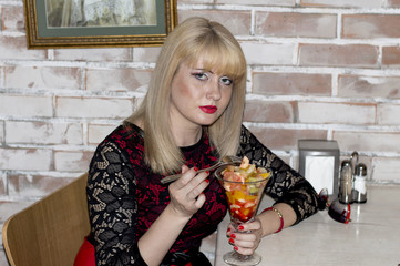 the woman in cafe eats fruit salad from a wine glass