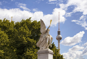 Winged woman statue on Schlossbruecke bridge with trees, cloudy sky and TV tower in the background. Designed by K. F. Schinkel in 1821 with sculptures of gods.