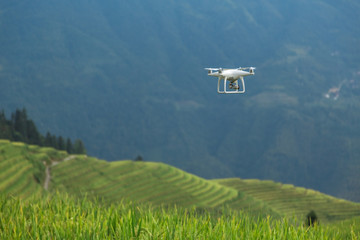 Hovering drone taking pictures of green hills. White drone flying over rice fields. Ping An Village, Longsheng County, China.