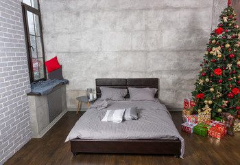 Stylish bedroom in loft style with grey colors and Christmas tre