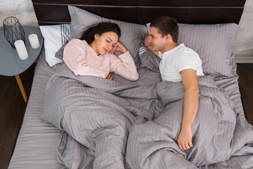 Young couple lying in the bed and wearing pajamas near bedside t