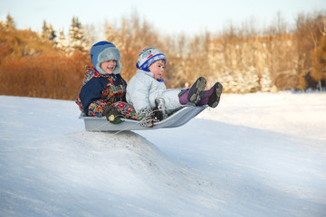 Two joyful child sledding down the hills in a winter day.