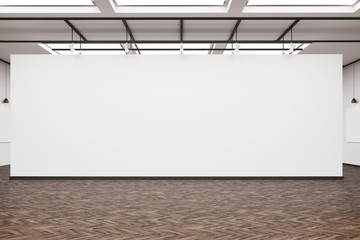 Large blank wall in an art gallery with dark wood floor