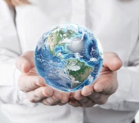 Close up of woman in white blouse holding planet