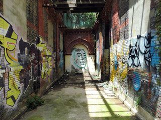 Jesus face graffiti down abandoned brick corridor
