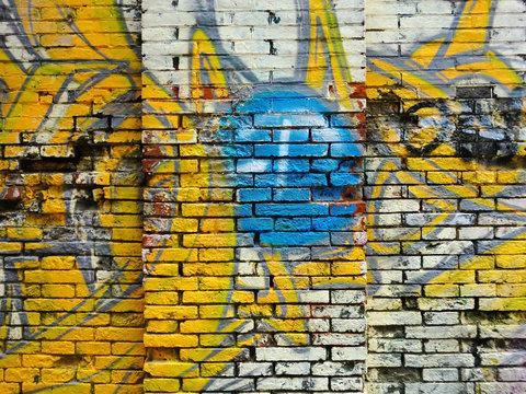 Brick building exterior wall texture with spray paint graffiti