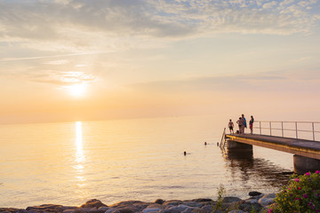 Sweden, Skane, Malmo, Sibbarp, People pier at sunset