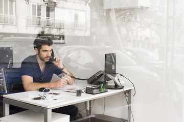 Man talking on telephone while sitting in the office