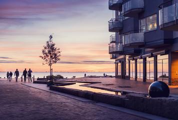 Sweden, Oresund Region, Skane, Malmo, Vastra hamnen, Silhouettes of people walking at sunset