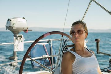 Croatia, Woman leaning against steering wheel of yacht